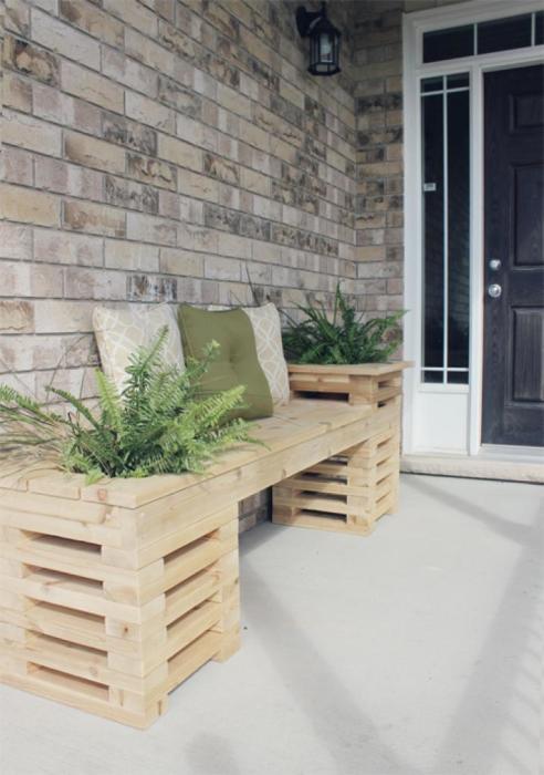 Деревянная скамейка из светлой породы древесины возле входа в загородный дом.